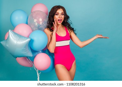 Beautiful sexy girl in pink bikini, in hands holding a bunch of balloons pink and blue. The concept of a holiday, fun, sale, stock in a store. Hand gesture promotion, empty space for text