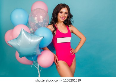 Beautiful sexy girl in pink bikini, in hands holding a bunch of balloons pink and blue. In the studio on a blue background. The concept of a holiday, fun, sale, promotion, offer