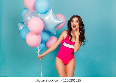 Beautiful sexy girl in pink bikini, in hands holding a bunch of balloons pink and blue. In the studio on a blue background. The concept of a holiday, fun, sale, promotion, offer, incredible emotions