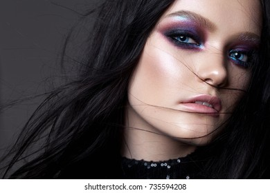 Beautiful sexy girl with professional evening makeup, perfect shining skin, dark hair. Trendy colorful smoky eyes.
