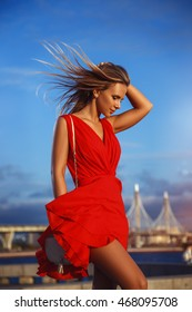 Beautiful sexy girl in a red dress walking and posing outdoors at sunset, curly hair blowing in the wind