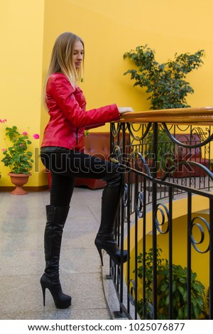 7414b45f4e01 A beautiful sexy girl in a red jacket and high-heeled boots stands in a