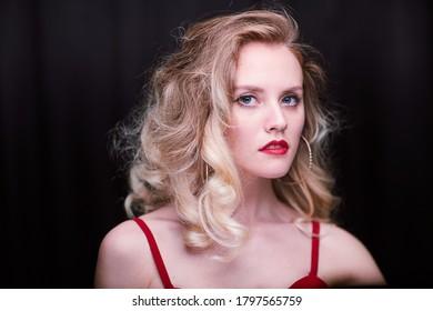 Schönes sexy Mädchen mit roten Lippen und lockig blondem Haar. Auf schwarzem Hintergrund