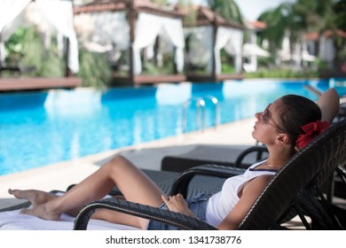 Beautiful and sexy girl relaxing near pool.