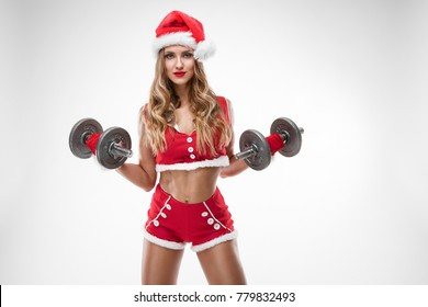 beautiful sexy girl in santa claus clothes doing workout with dumbbell over white background
