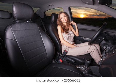 Beautiful sexy girl sitting behind the wheel and going on a trip Outdoors