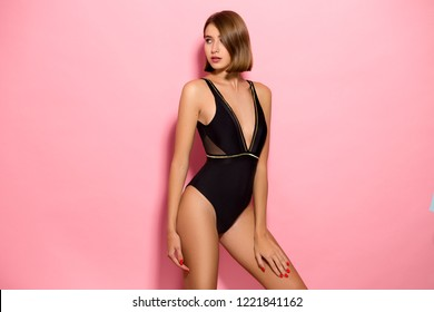 Beautiful sexy girl standing on a pink background in a colored bathing suit, smiling. Perfect for photo advertisements