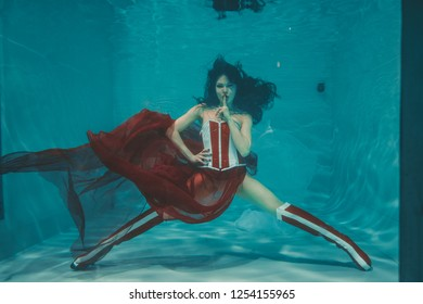 beautiful sexy girl swimming underwater in sporty style red and white fetish corset and over knee thigh high boots with heels
