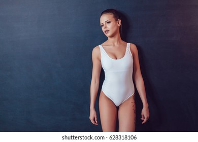 Beautiful sexy girl with tattoo in white bodysuit standing on a black background. Mock up.