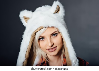 beautiful sexy girl wearing plaid shirt and white fur hat with funny ears. Close portrait on dark background