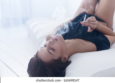 Beautiful sexy girl in a white interior on the bed smoking a cigarette