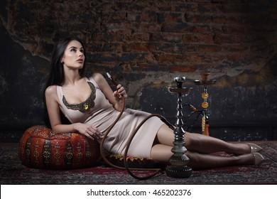 Beautiful and sexy glamorous woman smoking hookah