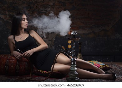 Beautiful and sexy glamorous woman smoking hookah