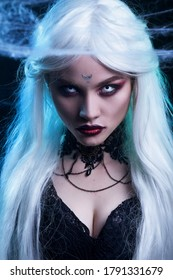 Beautiful sexy Halloween vampire woman portrait on dark magic background