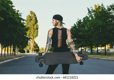 A beautiful, sexy hipster blonde with blue hair in tattoo stands with a longboard it is turned back on the street.