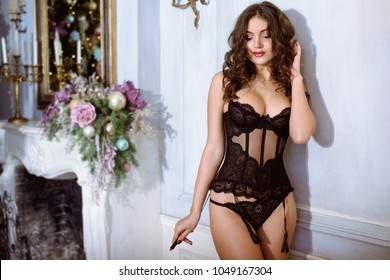 Beautiful sexy lady in elegant black panties and bra. Fashion portrait of model in glamorous outfit indoors. Beauty brunette woman with attractive body in lace lingerie. Female naked body in underwear