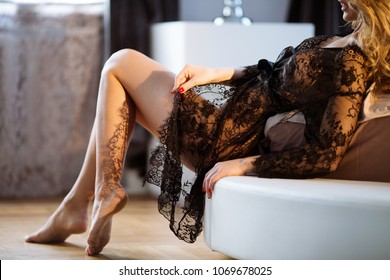 Beautiful sexy lady in elegant black robe. Close up fashion portrait of model indoors. Beauty blonde woman. Attractive female body in lace lingerie. Closeup fashionable naked girl in underwear