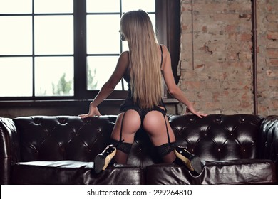 Beautiful sexy lady in elegant black panties and stockings. Portrait of fashion model girl indoors. Beauty blonde woman with attractive buttocks in lace lingerie. Female ass in underwear.