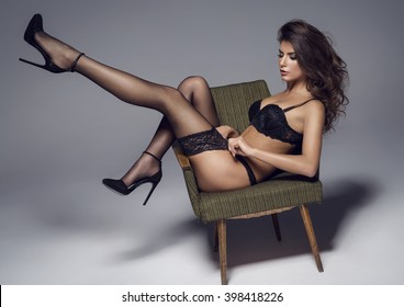 Beautiful sexy lady in elegant black lingerie and stockings. Beauty brunette woman with attractive buttocks in lace lingerie.