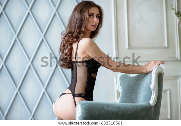Beautiful sexy lady in elegant black panties and bra. Fashion portrait of model indoors. Beauty brunette woman with attractive body in lace lingerie. Female ass in underwear. Close up naked girl