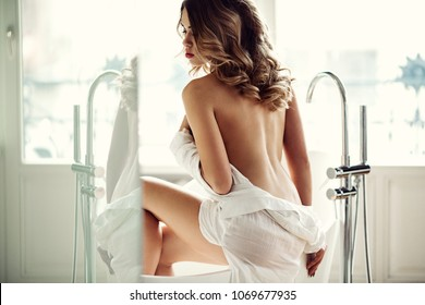 Beautiful sexy lady in elegant white shirt in a bathroom. Fashion portrait of model on a bath indoors. Beauty blonde woman with attractive body in lace lingerie. Female ass in underwear. Naked girl
