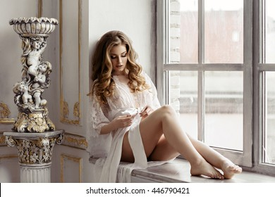 Beautiful sexy lady in elegant white robe. Close up fashion portrait of model indoors. Beauty blonde woman with attractive body in lace lingerie. Female ass in underwear. Closeup naked girl