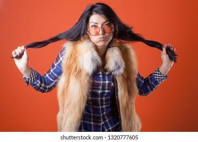 Beautiful sexy lady fashion pretty woman model pose wear plaid shirt and fur vest on the orange studio background