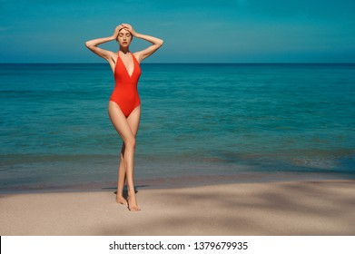 Beautiful sexy lady on tropical beach. Fashionable woman with slim perfect figure walking in front of blue sea. Model pose in red swimwear near the ocean. Relax portrait of young sunbathing beauty