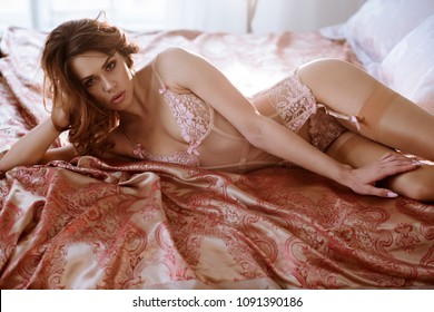 Beautiful sexy lady in pink panties and bra. Close up fashion portrait of model indoors. Beauty blonde woman. Attractive female body in lace lingerie. Closeup fashionable naked girl in underwear
