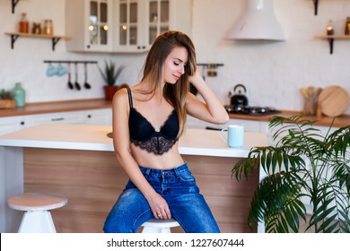 Beautiful sexy lady posing at home in elegant black bra and jeans. Fashion portrait of model indoors. Beauty woman with attractive body in lace lingerie