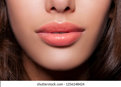 beautiful sexy lips. plump female lips with make-up - peach gloss lipstick. natural lips. beige color  - Image