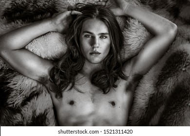 Beautiful sexy long hair male model portrait lying on fur bed.