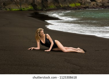 Beautiful and sexy long haired blonde woman lays on black sand beach in black swimsuit in Azores, Portugal