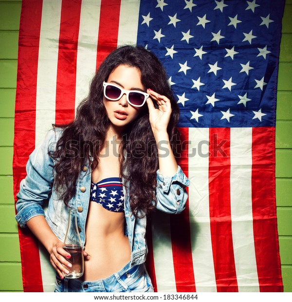 beautiful sexy long haired girl with glass bottle of water and skateboard against american flag sets sunglasses
