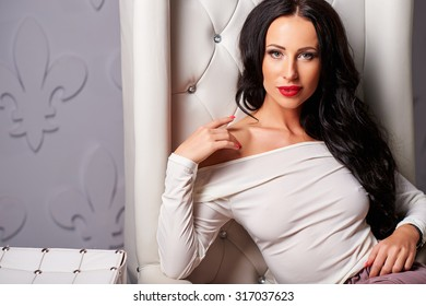 Beautiful, sexy, luxurious, strong, successful, intelligent woman brunette with long curly hair, red lips, clean, healthy, youthful skin and piercing eyes in a white leather chair  in the Studio