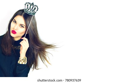 Beautiful sexy model Gil holding funny crown on stick isolated on white background. Joyful young fashion brunette woman with bright make up, red lips and nails
