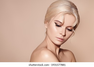 Beautiful sexy model with retro style make-up, clean skin, blond hair bun on beige background. Elegant woman model in femininity pose with fashion make-up, hairstyle