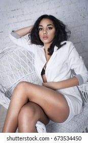 Beautiful sexy mulatto girl sitting in white wicker chair indoors