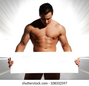 beautiful and sexy naked and well trained sports man is holding and displaying a white board in his hands on were you can write text