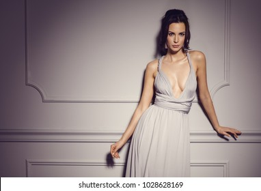 Beautiful sexy natural woman wear evening dress and posing on grey background