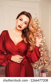 Beautiful sexy plus size model woman in glamour red dress, christmas tree on a background. Curly brunette hair and red lips. Copy space