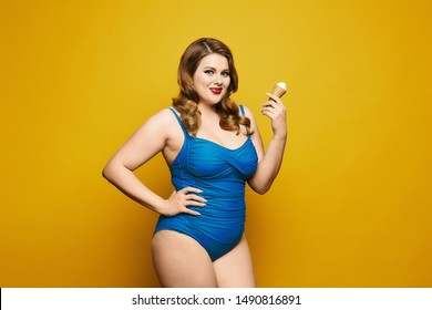 Beautiful and sexy plus size model girl, with stylish hairstyle and red lips, in fashionable blue swimsuit eating tasty ice cream and posing at the yellow background, isolated