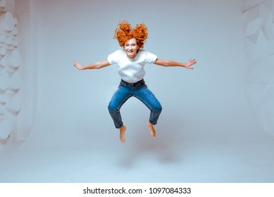 Beautiful sexy red hair smiling woman wearing high waist jeans and white t-shirt, high heels posing in studio. Colorful bright background. Isolated on white. Full-length portrait. Studio shot.