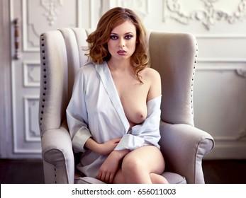 Hermosa mujer de pelo rojizo sexy en pantalones blanco