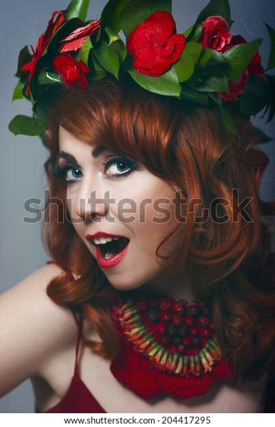 Beautiful sexy red-haired girl in a red dress with makeup and red lips with wreath  with flowers in her hair decoration of flowers around his neck smiling happy