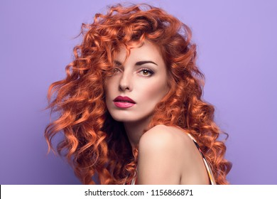 Beautiful Sexy Redhead Woman. Care spa and beauty concept. Sensual Girl with Fashion Trendy Makeup, Wavy Curly Hairstyle. Close up female Face Portrait with Perfect Skin on Purple