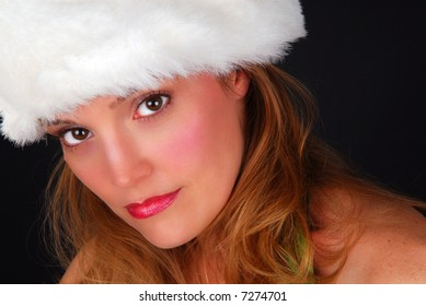 Beautiful, sexy and sensual blond model low key portrait with red Christmas holiday hat with fur trim.