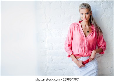 Beautiful sexy sensual blonde girl in the pink jacket in the Studio against the wall