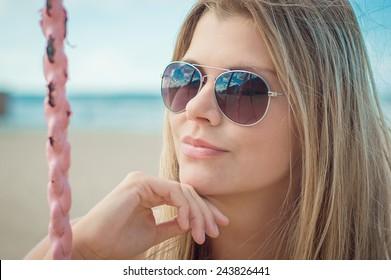 Beautiful sexy slim girl portrait. She is sunbathing on the beach on swing near sea waves