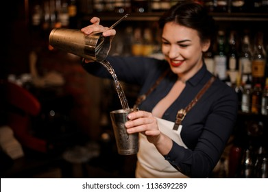 Beautiful sexy smiling barmaid with a deep neckline making a fresh summer cocktail in a shaker
